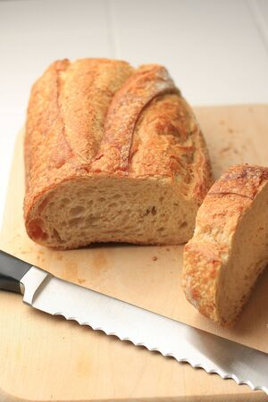 Loaf of bread on cutting board with knife Stock Photo