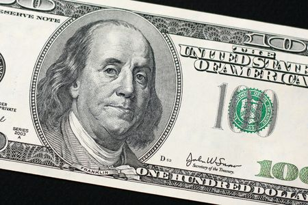 US $100 bill isolated on black background