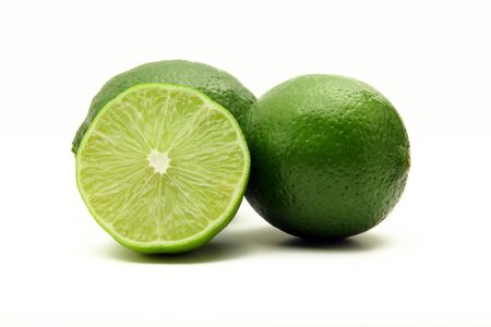 Three green juicy limes isolated on white background, one cut in half Stock Photo