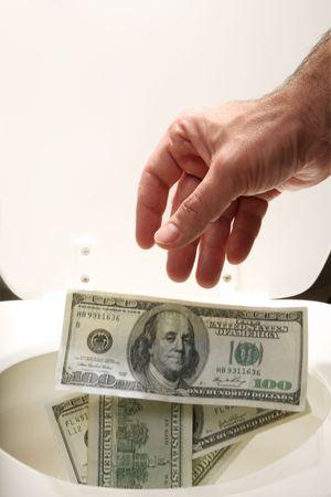wasteful: Man throwing US $100 bills into toilet Stock Photo