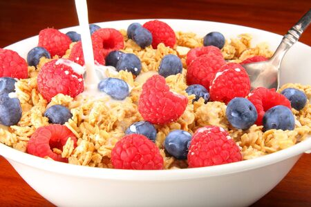 Delicious bowl of granola cereal with raspberries, blueberries and milk Stock Photo
