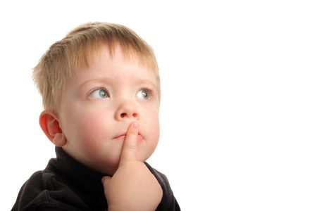 Cute young boy with blonde hair and green eyes looking up with finger on lips, wondering.