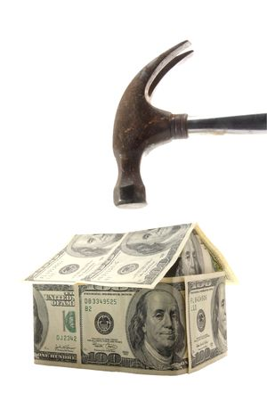 Hammer about to smash a home made out of US $100 bills - concept photo of home mortgage crisis