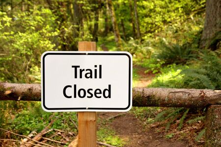 Trail closed sign along path in the woods