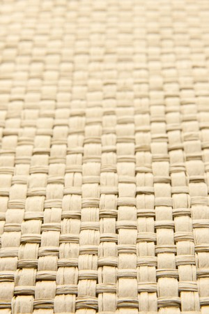 Close up of abstract yellow woven thatch textured background, shallow depth of field