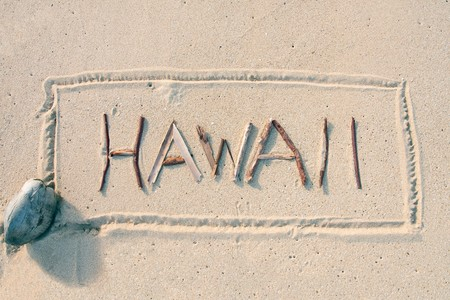 Hawaii written with sticks on a sandy beach with coconut Stock Photo