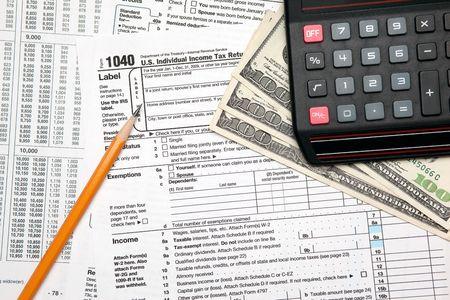 Tax time - Closeup of U.S. 1040 tax return with pencil and calculator