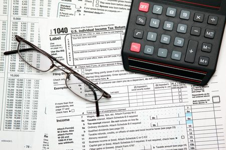 Tax time - Closeup of U.S. 1040 tax return with calculator and glasses photo