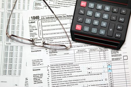Tax time - Closeup of U.S. 1040 tax return with calculator and glasses Stock Photo