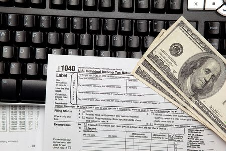 Tax time - Closeup of U.S. 1040 tax return with $100 bills and computer keyboard