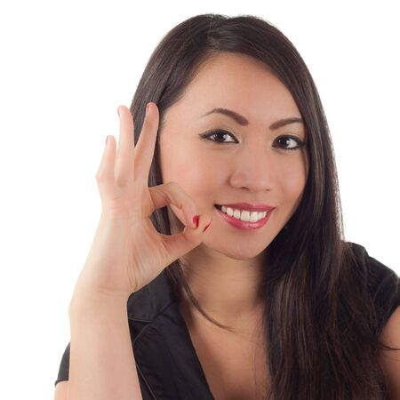 Cute young asian woman smiling and showing okay sign with finger and thumb