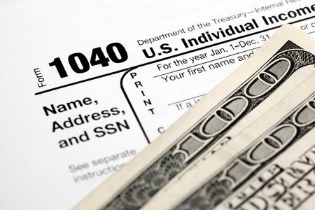 refund: Tax time - Closeup of U.S. 1040 tax return with $100 bills