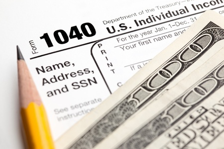 tax bills: Tax time - Closeup of U.S. 1040 tax return with pencil and money Stock Photo