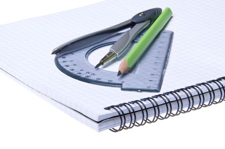 Compasses, protractor and pencil on copybook isolated on white background