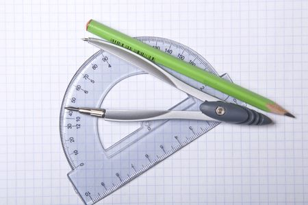 compass, protractor and pencil on copybook
