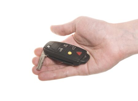 Hand with open cars key isolated over white photo
