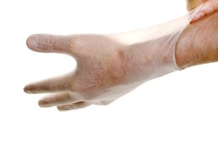Doctor pulling on surgical glove isolated over white
