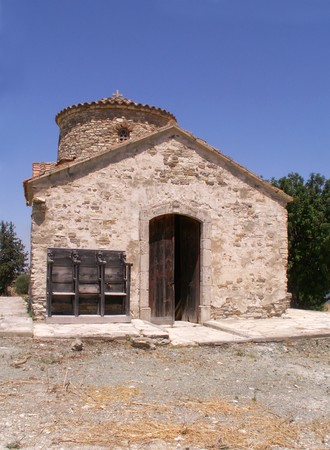 Old small stone church on a hill overlooking protaras on the island of Cyprus under blue sky  photo