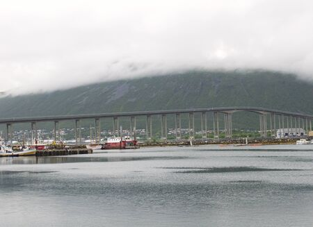 artic circle: bridge through fjord under clouds in Tromso Stock Photo