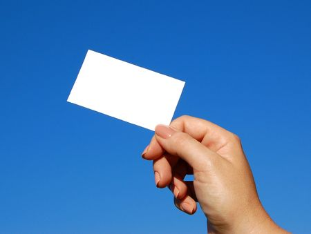 business card for text being held with blue sky in background