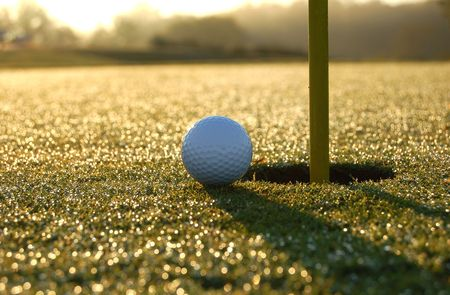 close golf shot on a dewy green with the morning sun in the background