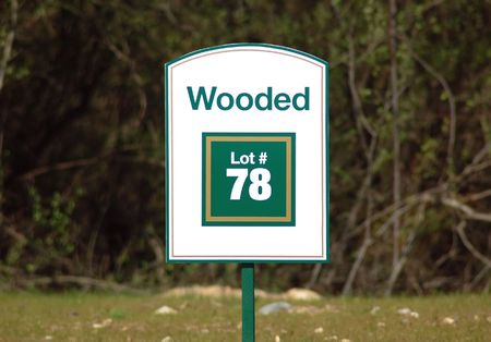 housing lot: Real estate sign on a new lot in the woods Stock Photo