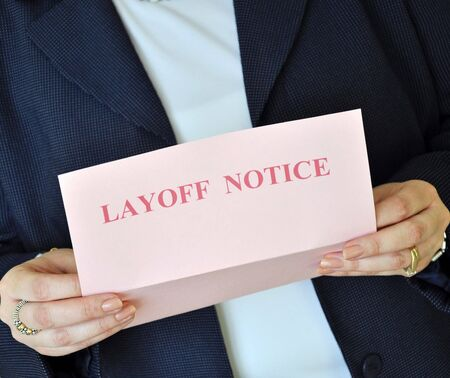 layoff: Female executive reading a layoff notice from her employer Stock Photo