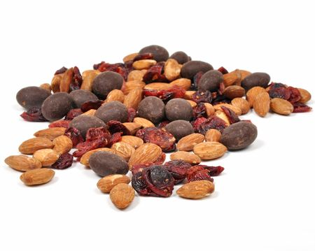 Closeup of a snack consisting of nuts, dried fruit and chocolate on a white background