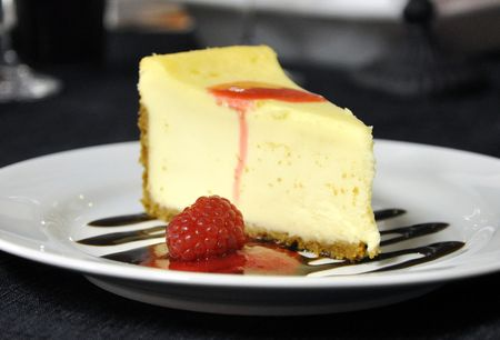 A slice of cheesecake with chocolate and raspberry sauce