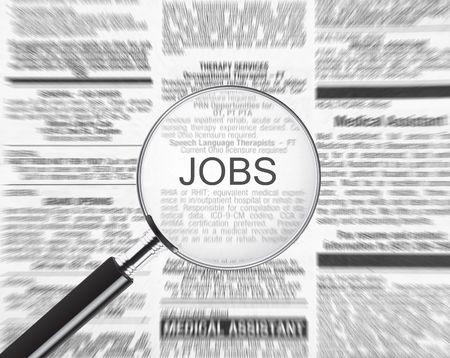 Anuncio de puestos de trabajo en un periódico a través de una lupa