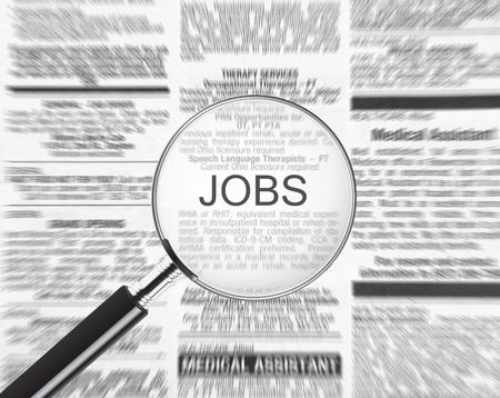 Jobs ad in a newspaper through a magnifying glass Stock Photo