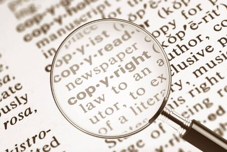 The word copyright from the dictionary under a magnifying glass 版權商用圖片