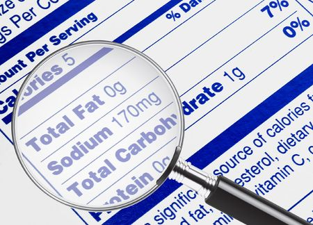 grasas saturadas: Informaci�n de nutrici�n est�n estudiando bajo una lupa  Foto de archivo