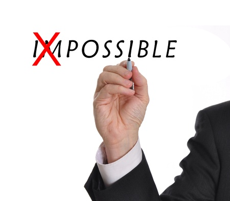 Businessman in suit drawing text of the word impossible with red mark through part of the word making it now possible