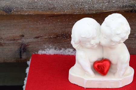 kissing angels on a wooden, red and snow background, on the right, horizontal greeting Valentines Days card, Saint Valentines Day, Feast of Saint Valentine, February 14 Stock Photo