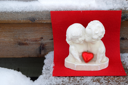 kissing angels on a wooden background, red and snow background, horizontal greeting Valentine's Day's card, Saint Valentine's Day, Feast of Saint Valentine, February 14