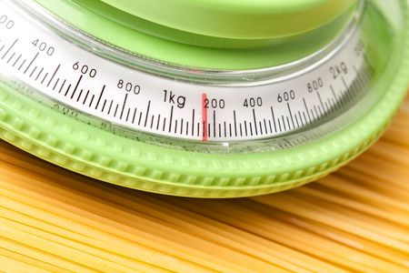 ingest: kitchen scale with spaghetti on the table Stock Photo
