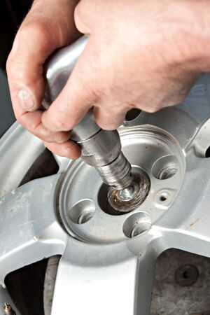 aligning: Mechanical repairs a tire in the garage. Stock Photo