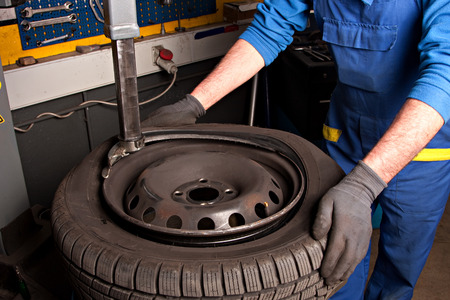 setup man: Mechanical repairs a tire in the garage. Stock Photo