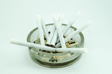 nicotine: Glass ashtray with cigarettes, health warnings, nicotine addiction