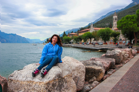 womankind: Woman sitting on a stone at the shores of Lake Garda, near Castelletto, Italy