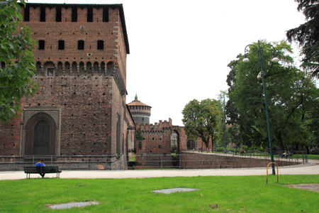 moat wall: fragment of the fortress wall, the moat and corner tower of the Sforzesco Castle Editorial