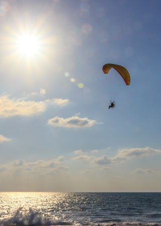 motorized: parachute jumper on motorized parachute flying over the sea at sunset