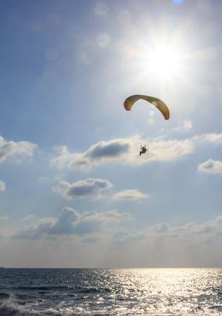 MOTORIZADO: paracaidista en el paracaídas motorizado volando sobre el mar al atardecer Foto de archivo
