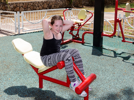 simulator: Girl in a sports simulator training on the playground outdoors