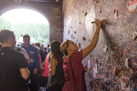juliets: Verona, Italy, September 26, 2015: Young girl write a letter to Juliet on the wall in the passage to Juliets house in Verona, Italy