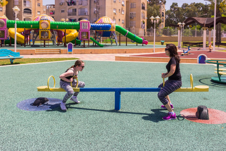 playground ride: mother and daughter ride on a swing at the city playground Stock Photo
