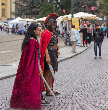 Verona, Italy, September 27, 2015: Man and woman dressed as legionnaires expect wishing to be photographed with them in Piazza Bra, in Verona, Italy