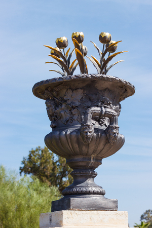 scenical: decorative vase with gold tulips in city park