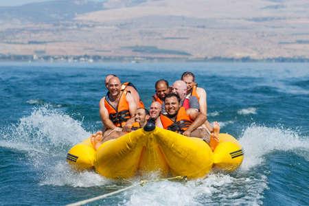 Tiberias, Israel, 27. September 2016: Gruppe junge Männer, die auf einer aufblasbaren Attraktion schwimmt auf See Genezareth in Tiberias, Israel